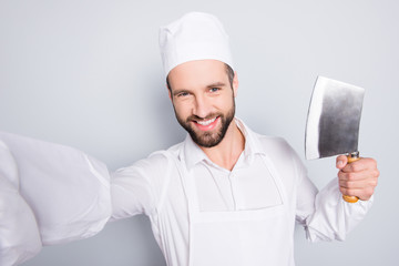 Self portrait of cheerful positive man shooting selfie on smart phone during break, pause, time out, having metal cleaver in hand, isolated on grey background