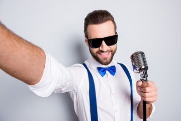 Self portrait of stylish elegant singer wearing bowtie shirt suspenders shooting selfie on front camera holding mic isolated on grey background