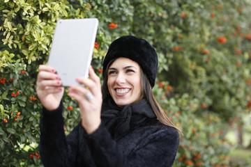 Donna mora vestita di nero con il colbacco si fa un selfie con il suo tablet - sfondo parco