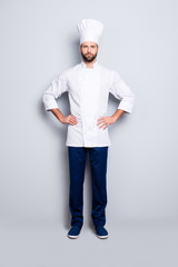 Full size fullbody portrait of attractive harsh chef cook with stubble in beret, holding arms on waist, isolated over grey background, looking at camera