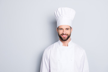 Portrait of cheerful joyful chef cook with stubble in beret and white outfit looking at camera isolated on grey background