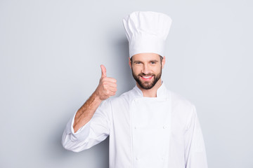Portrait of cheerful joyful chef cook with stubble in beret, white outfit showing thumb up, approve menu, yes, done sign isolated on grey background, advertisement concept