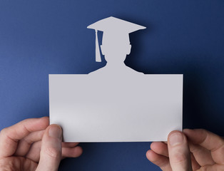Graduation card. Male hands holding blank card with graduate cutout.