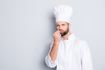 Portrait with copy space, empty place for advertisement product of handsome chef cook in beret, white outfit making bellisimo symbol, sign with pout lips and fingers, isolated on grey background