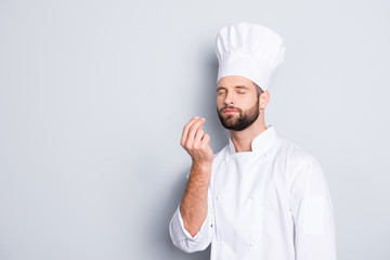 Portrait with copyspace, empty place for advertisement, product of attractive chef cook in beret with close eyes, white outfit making bellisimo symbol, sign with fingers, isolated on grey background