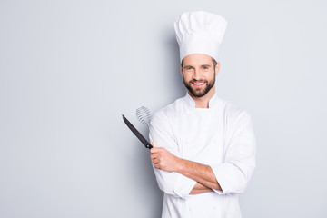 Portrait of positive toothy chef cook in beret, white outfit with stubble having tools in crossed arms looking at camera isolated on grey background
