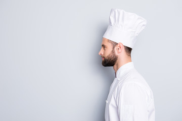 Profile side view half face portrait with copyspace empty place for advertisement product of concentrated, handsome chef cook in beret and white outfit isolated on grey background