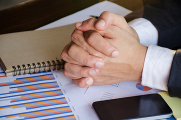 Business concept image. A business man is listening in a meeting with his hands crossed on the table. He is like praying. Business outfit