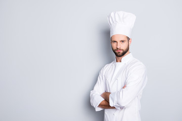 Portrait with copy space, empty place for advertisement, product of harsh virile chef cook with stubble in beret, white outfit having his arms crossed, isolated on grey background