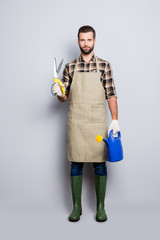 Full size body portrait of trendy stylish gardener with stubble, hairstyle, looking at camera, isolated over grey background, having scissors for plants and watering can in arms