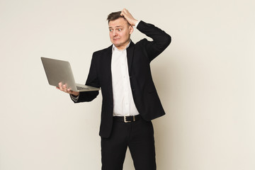 Disappointed caucasian businessman using laptop