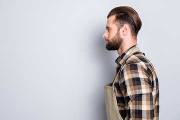 Profile side view portrait with copy space, empty place for product of attractive, virile, harsh farmer with stubble, uniform, hairstyle, isolated on grey background, advertisement concept