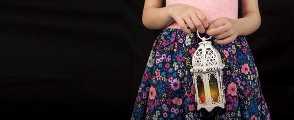 Happy young Muslim girl holding Ramadan lantern