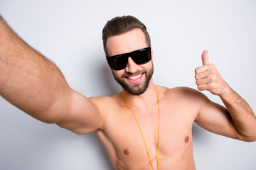 Self portrait of cheerful joyful lifeguard with stubble shooting selfie on front camera showing thumb up sign isolated on grey background