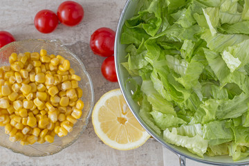 A colander with green salad. Background: cherry tomatoes, lemon and corn. From above.