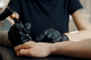 tattoo process machine close-up. master prepares for procedure of drawing