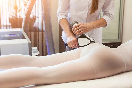 Masseur making hardware massage on patient's legs in white suit