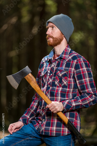 e8161e4532a vertical portrait of a lumberjack with an ax in the summer forest ...