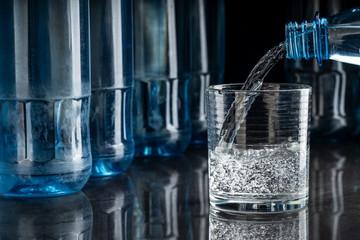 Mineralwasser in ein Glas eingeschenkt auf spiegelndem Tisch, Hintergrund