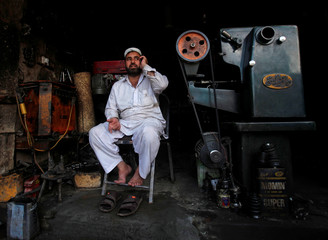 A technician talks on a phone near a lathe machine at a workshop during a power breakdown in Peshawar