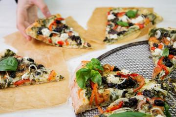 Freshly baked italian vegetarian pizza slices on a metal mesh pan