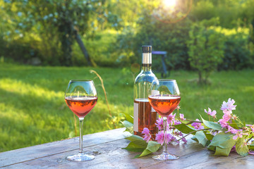 French art of living/Bottle of pink wine and two wineglasses on a rustic wooden table in a spring garden