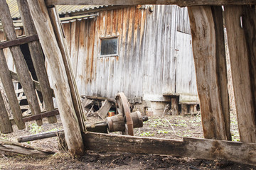 Ruins of old ranch in countryside. Broken wooden barn and wheel from the cart