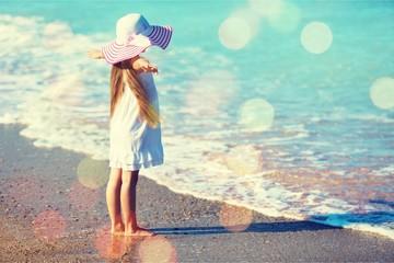 Beautiful girl in white dress on beach