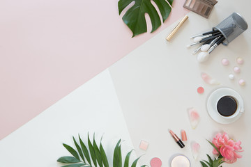 Pastel office table desk with computer laptop, green palm leaves, flowers, clipboard and beauty accessories, top view and flat lay. Home fashion women office workspace isolated on pink background.