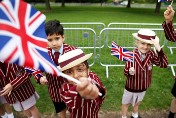 School children in uniform wave Union Flags outside Windsor Castle ahead of Britain's Prince Harry and Meghan Markle's wedding, in Windsor