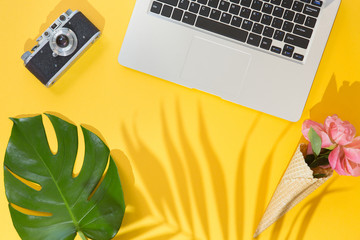 Flat lay design of yellow background with labtop, photo camera, green palm tropical leaf and flowers, top view. Summer background, vacations and holidays, trip and travel planning concept