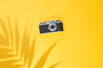 Top view of summer background with Tropical palm tree leaf shadow and vintage photo camera on a trendy bright yellow background, flat lay