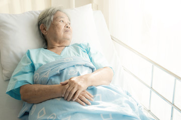 Elderly patient alone in bed. Alone and stress, missing her grand children. Looking at window. Very senior, old chinese woman.