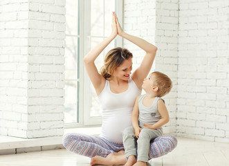 A young pregnant woman engaged in fitness and yoga with the child.