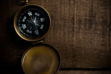 Bronze compass on aged, distressed wooden tabletop