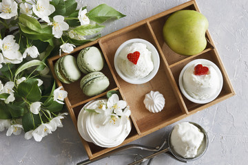 Close-up photo of cold cups of ice-cream with macaroons, green apple in wooden box and beautiful fresh flowers on grey table background. Top view