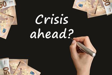 Crisis ahead question handwritten on blackboard by a woman hand. Financial crisis, European stock market crash