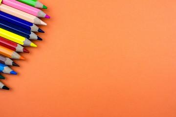 Color Pencils set on orange tone color paper. Empty space for text and design. Minimalism concept