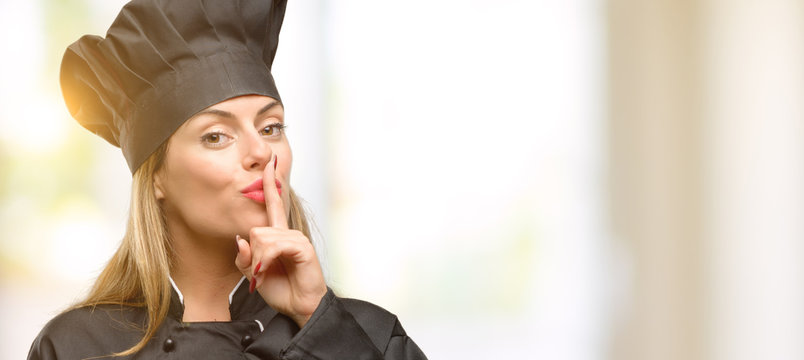 Young cook woman with index finger on lips, ask to be quiet. Silence and secret concept