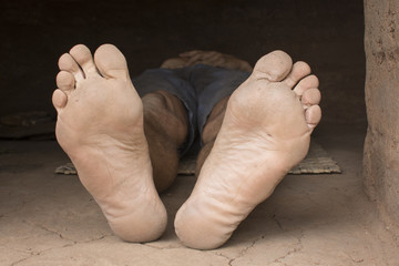 Bare feet of impoverished man resting in hut