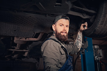 Bearded auto mechanic in a uniform repair the car's suspension with a wrench while standing under lifting car in repair garage.