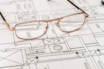 Engineer's drawing with spectacles, close up .