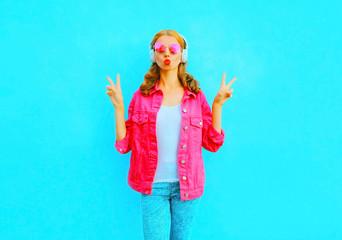 Fashion pretty woman listens to music in wireless headphones in pink denim jacket