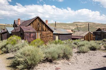 Verlassene und verfallene Holzhäuser einer amerikanischen Geisterstadt in einer staubigen und weiten Ebene umrahmt mit Wüstenbewuchs,  Buschwerk,  sanften Hügeln und blau weissem Himmel