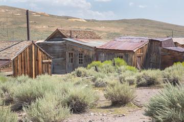 Trockene, sandige und staubige Ebene mit Buschwerk und verlassenen, verfallenen Holzhäuser einer amerikanischen Geisterstadt