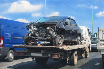 wrecker transports broken car