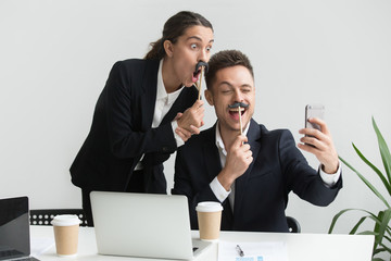 Colleagues having fun, taking self-portrait with mustache accessory, making silly faces, playing childish during work break. Coworkers laughing, wearing party outfit while making photo with smartphone