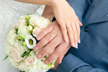 Hands of newlyweds with wedding rings on a bouquet of the bride.