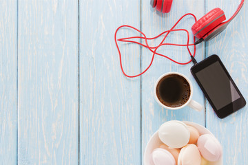 the marshmallow is next to the phone and red headphones and a Cup of black coffee. Coffee-break. Pleasant music.