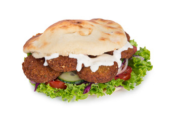 falafel with fresh vegetables in pita bread on white.